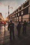 Policía que cruza la calle durante la puesta del sol Imágenes de archivo libres de regalías