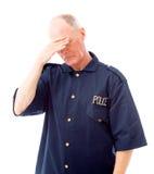 Policía que sufre de dolor de cabeza Imágenes de archivo libres de regalías
