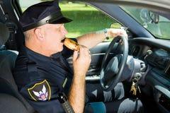 Policía Snacking en el trabajo Imagenes de archivo