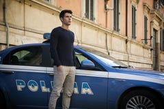 Policía italiano que se coloca junto a un coche patrulla Imágenes de archivo libres de regalías
