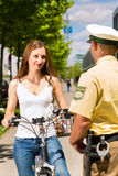 Policía - mujer en la bicicleta con el oficial de policía Foto de archivo