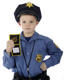 This is the Police!. An adorable young elementary boy showing his badge while wearing a police uniform.  On a white background Royalty Free Stock Image