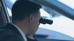 Police agent looking through binoculars from car, detective investigation, news. Stock footage stock video footage