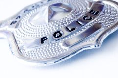 Police badge. Close-up of a police metal badge over white background Royalty Free Stock Photo