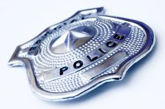 Police badge. Close-up of a police metal badge over white background Stock Image