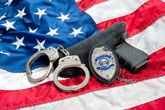 Police badge and gun. Police badge, gun and handcuffs on an American flag symbolizing law enforcement in the United States royalty free stock photo