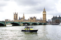 Police boat on the river thames outside parliment. London - March 2012 - A Metropolitan Police river boat cruises along past the houses of parliment during the Stock Photos