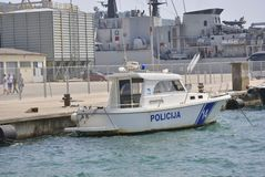 Police boat. Zelenika town, Montenegro – June 18, 2016: Police boat with military ship on the background ancored in port of Zelenika town Royalty Free Stock Photos