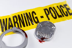 Police Brutality. Police warning tape with blood covered police badge and handcuffs Stock Photography