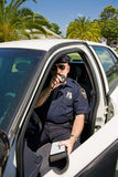 Police - Calling In Tag. Police officer in his car calling in a license number on his radio Royalty Free Stock Photo