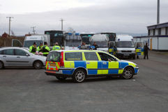 Police Car. Side on with various police vehicles in the background at the scene of a public disturbance Stock Photography