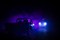 Police car chasing a car at night with fog background. 911 Emergency response police car speeding to scene of crime. Stock Photo