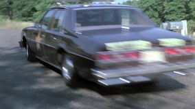 Police car chasing man in station wagon on country road stock footage