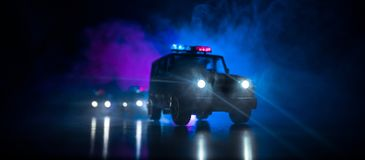 Police car chasing a car at night with fog background. 911 Emergency response police car speeding to scene of crime. Selective foc. Police cars at night. Police stock photography