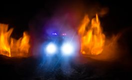 Police car chasing a car at night with fog background. 911 Emergency response police car speeding to scene of crime. Selective focus royalty free stock photo