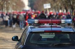 Police car during the demonstration with the rioters. Police car during the demonstration with many rioters at public urban park Stock Photo