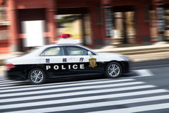 A police car driving on city streets Royalty Free Stock Photo