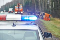 Police car with a flasher at lorry crash. Police car with a flasher in front of damaged lorry trailer in ditch of highway Royalty Free Stock Image