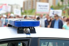 Police car flashing lights in focus, blurred protesters in the background. Police car flashing lights in focus with crowd out of focus in the background stock photos