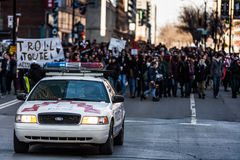 Police Car in front of the Protesters controlling the Traffic Stock Photo