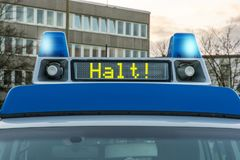Police car with the German word for stop! in the display panel to be switched on blue rotating light stock image