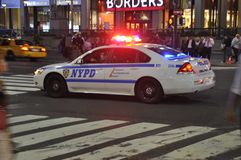 A police car going on a emergenvy call with light and siren. A New York City police car rides on a emergency call with lights and siren royalty free stock photo
