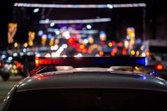 Police car lights at night in city with selective focus and bokeh.  stock photos