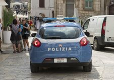 Police car on narrow street in the City of Ostuni, The White City, Apulia, Italy. Pictured is a blue FIAT Police car on a narrow street in the city of Ostuni Stock Photo