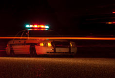 Police car at night. With emergency lights on, tail lights going by Royalty Free Stock Images