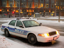 Police Car Parked at Night in Snowfall. A Police car parked in winter downtown area at night time with snow falling Stock Image