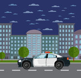 Police car on road in urban landscape Royalty Free Stock Image