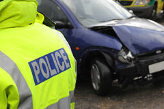Police at a car crash. A police officer at the scene of a collision. Good depth sharp POLICE soft focus vehicle as backdrop Stock Photos