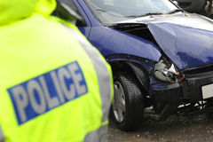 Police at a car accident. A police officer at the scene of a collision. Selective focus. Good depth sharp focus vehicle as backdrop with out of focus POLICE logo Stock Photography