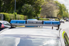 Police Car and Traffic. Light bars on unidentified British police vehicle monitoring traffic on a busy main road or highway with defocussed traffic in the Stock Photography
