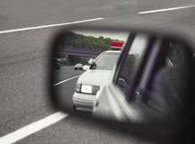 Police car viewed through sideview mirror. Police car viewed through side-view mirror Stock Image