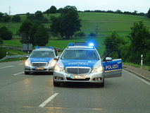 Police cars barricade highway. German police cars (Mercedes) in action - barricading a rural highway at evening Royalty Free Stock Photo