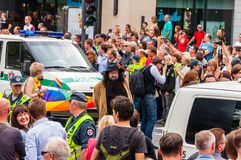 Police cars driving during the Pride parade on Gedimino street full of people. Event celebrating lesbian, gay, bisexual,. Vilnius, Lithuania - July 27, 2013 royalty free stock image