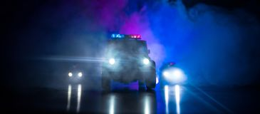 Police car chasing a car at night with fog background. 911 Emergency response police car speeding to scene of crime. Selective foc. Police cars at night. Police royalty free stock images