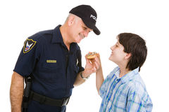 Police Community Relations. Adolescent boy giving a donut to a friendly police officer.  Isolated on white Royalty Free Stock Photos