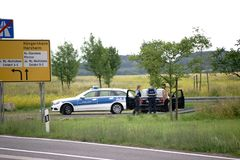 Police control on the roadside. Mainz, Germany - June 17, 2018: A police ambulance with two police officers carry out a control of a car driver on the roadside Stock Photos