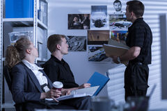 Police cooperating with private detective. During investigation Stock Photos