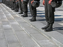 Police cordon in black uniform, hard hat (helmet),. Police cordon in black uniform with hard hat (helmet) on the stone staircase, security details royalty free stock photos