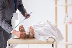 The police coroner examining dead body corpse in morgue. Police coroner examining dead body corpse in morgue royalty free stock photo