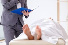 The police coroner examining dead body corpse in morgue. Police coroner examining dead body corpse in morgue royalty free stock images