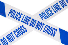 Police crime scene tape cross and white copy space. Close up of blue police line do not cross crime scene tape forming a cross with white copy space Stock Photo
