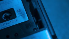 Police custody interview audio cassette in a retro 1970s portable recorder stock footage