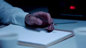 Police Custody Interview Room - Detective Fiddling with Pen. Police custody interview room, a detective fidgets with a pen as he listens to a suspect talk stock footage