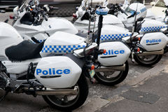 Police cycles lined behind police car. Stock Images