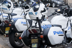 Police cycles lined behind police car. Stock Photos
