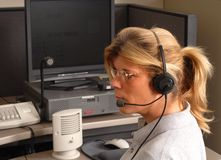 Police dispatcher at console. A police dispatcher sitting at a dispatch console Royalty Free Stock Photos